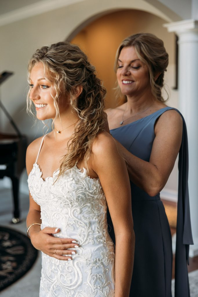 Bride in front of her mom, who is zipping up her wedding dress