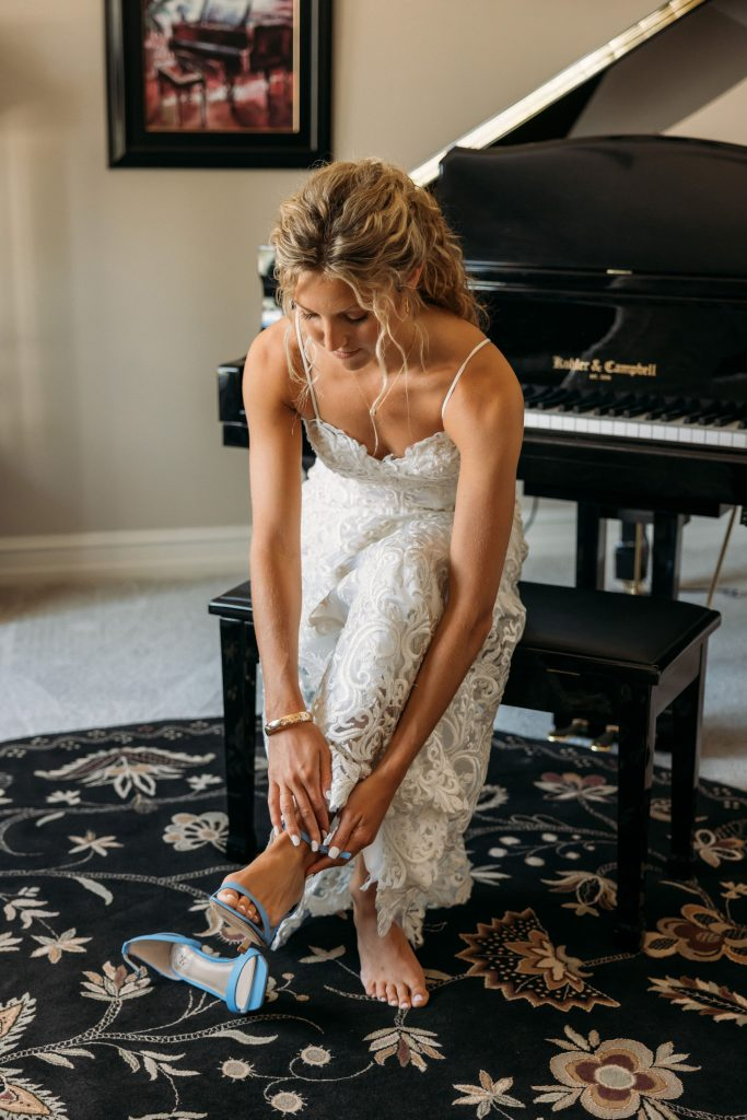 Bride adjusts her shoe sitting by a piano