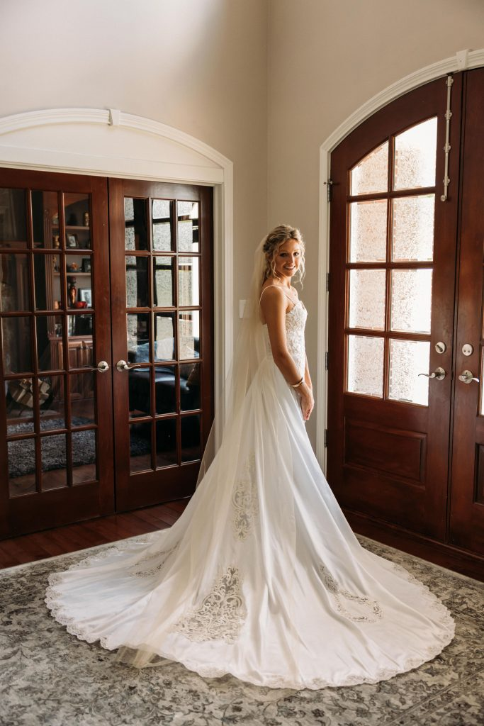 Bride stands close to a door, twisting her body towards the camera, the train of her dress spread out.