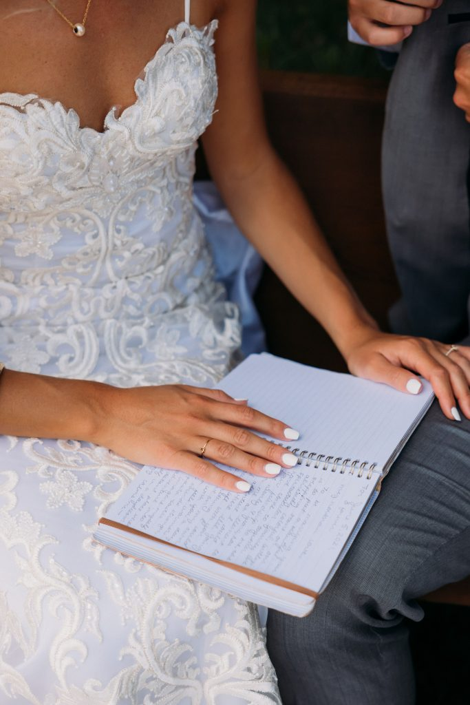Bride, sitting down in her lace wedding dress reading her vows