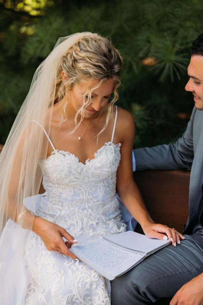 Bride and groom sharing vows while sitting on a bench