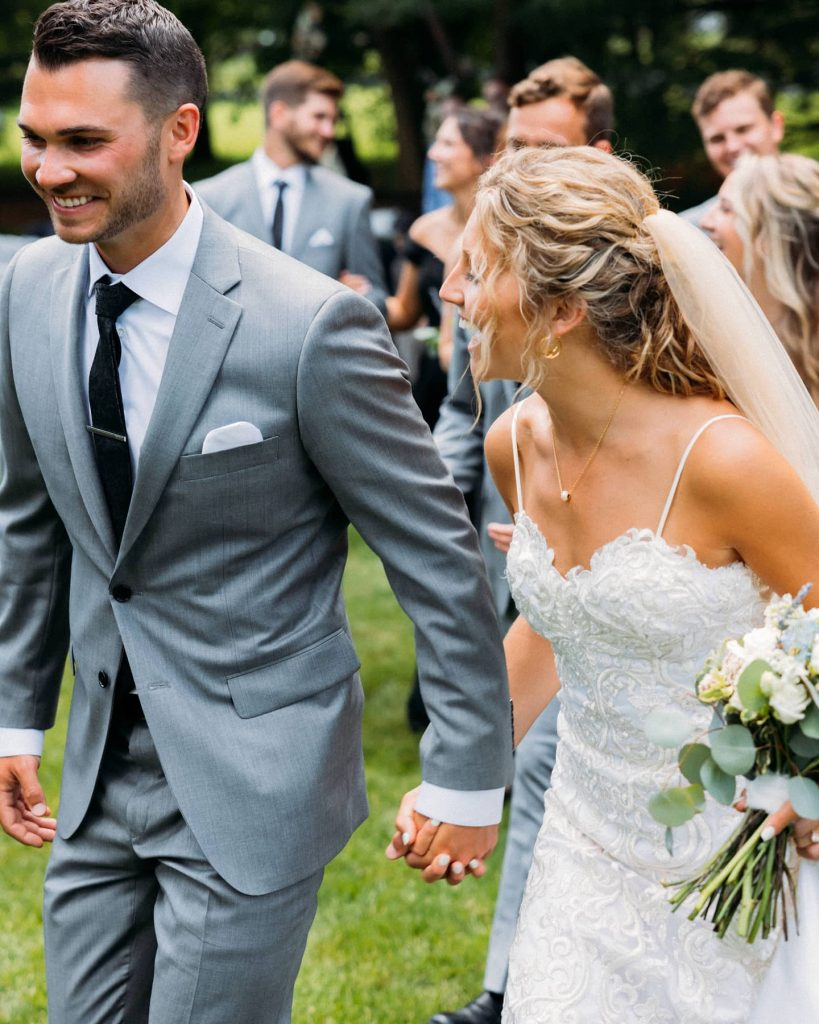 White bride and groom holding hands laughing and walking