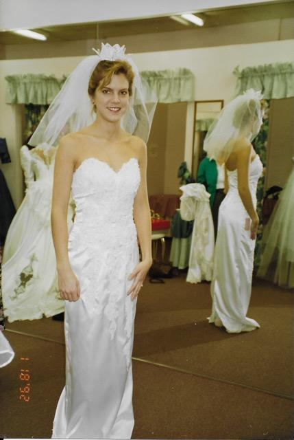 Woman in a wedding dress shop, trying on a white wedding dress